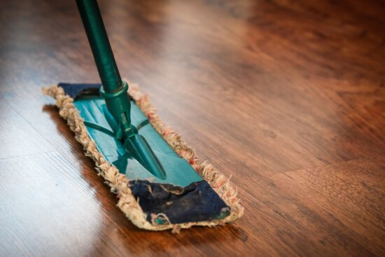 a large, rectangular swiffer-type mop glides across gleaming wooden floor. broom is teal.