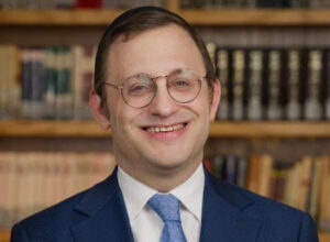 a headshot of rabbi linzer smiling with a library in the background