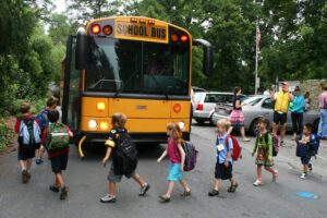 a school bus stopping on a road with its doors open while a line of small children with backpacks walk in a line to get onto the bus