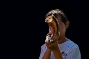 young boy in a white t-shirt blowing a shofar with a black background