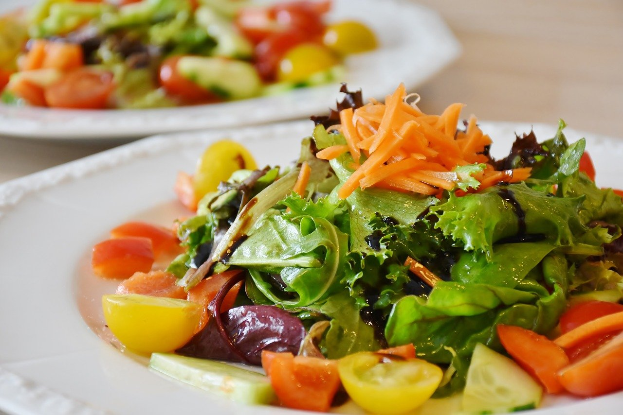 picture of a green salad with cherry tomatoes and carrots on a white plate on what looks like the table of a restaurant. looks delicious.